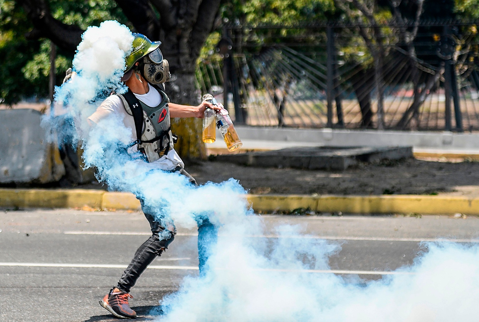 An anti-government protester throws Molotov cocktails during clashes with security forces near La Carlota military base in Caracas during May Day on May 1 after a day of violent clashes on the streets of the capital spurred by Venezuela's opposition leader Juan Guaido's call for the military to rise up against President Nicolas Maduro. MATIAS DELACROIX/AFP/Getty Images