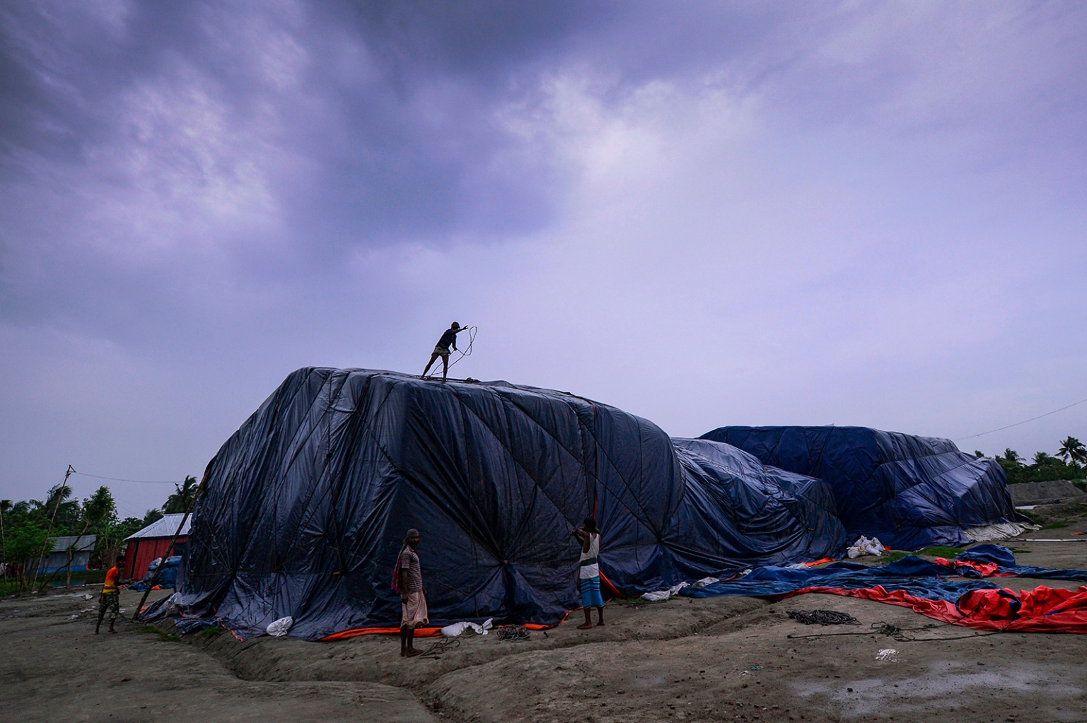 Bangladeshi workers cover a pile of fertilizer with a plastic sheet in Khulna on May 3 as Cyclone Fani barrels northeastward into West Bengal state and toward Bangladesh. MUNIR UZ ZAMAN/AFP/Getty Images
