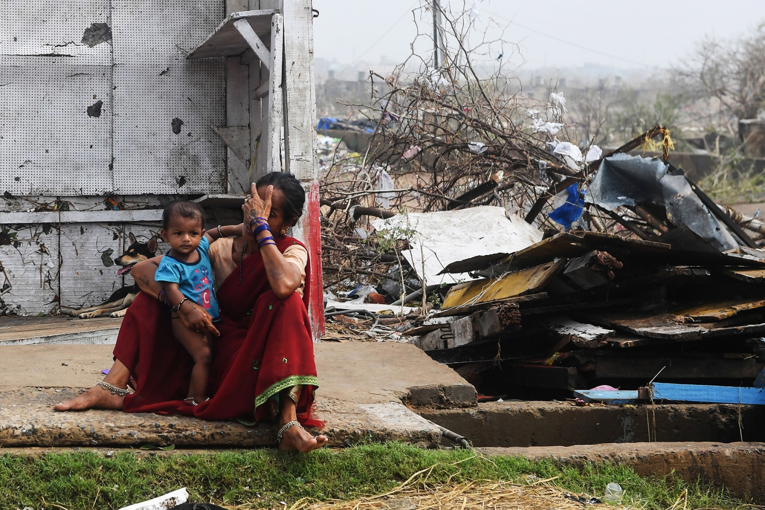 An Indian woman sits with her child next to storm-damaged buildings in Puri in the eastern Indian state of Odisha on May 4 after Cyclone Fani swept through the area. DIBYANGSHU SARKAR/AFP/Getty Images