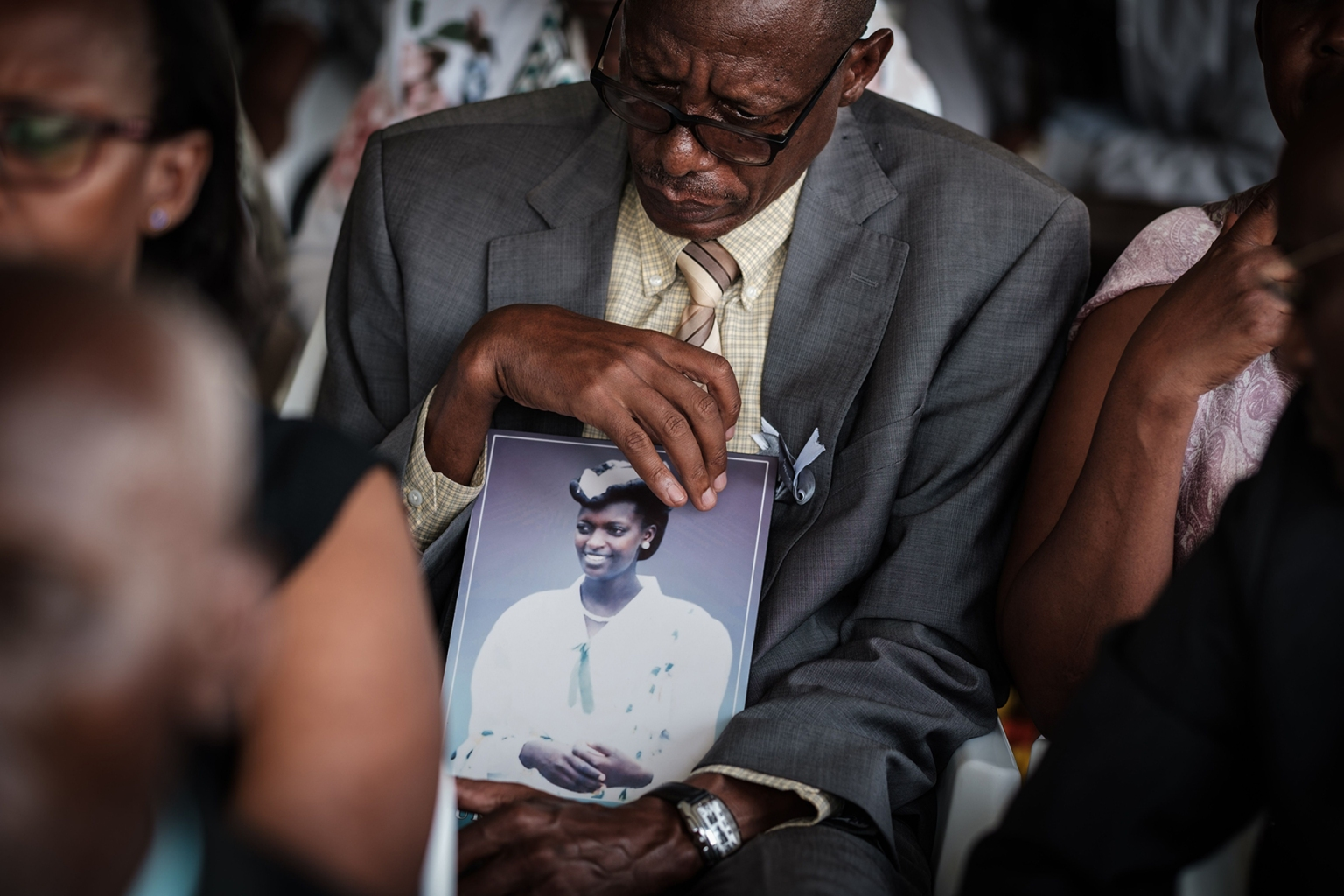 Vianney Rusanganwa, 61, holds a portrait of his late wife Liberatha Mukangira who died at age 31 in 1994, during the mass funeral to bury 81 coffins containing newly discovered remains of victims of the Rwandan genocide at the Nyanza Genocide Memorial near Kigali on May 4. YASUYOSHI CHIBA/AFP/Getty Images