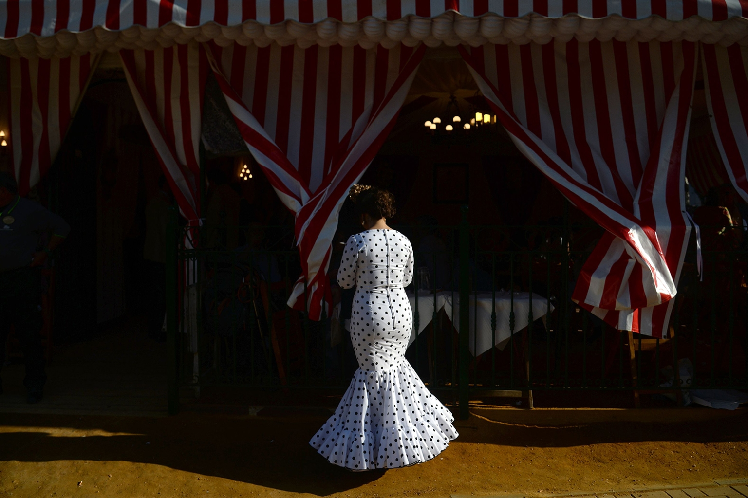 "A woman in traditional Sevillian dress stands in front of a stall during the ""Feria de Abril"" (April Fair) in Seville on May 6. The festival dates back to 1847 when it was organized as a livestock fair but has turned into a week of flamenco dancing, music, and bullfighting. CRISTINA QUICLER/AFP/Getty Images"