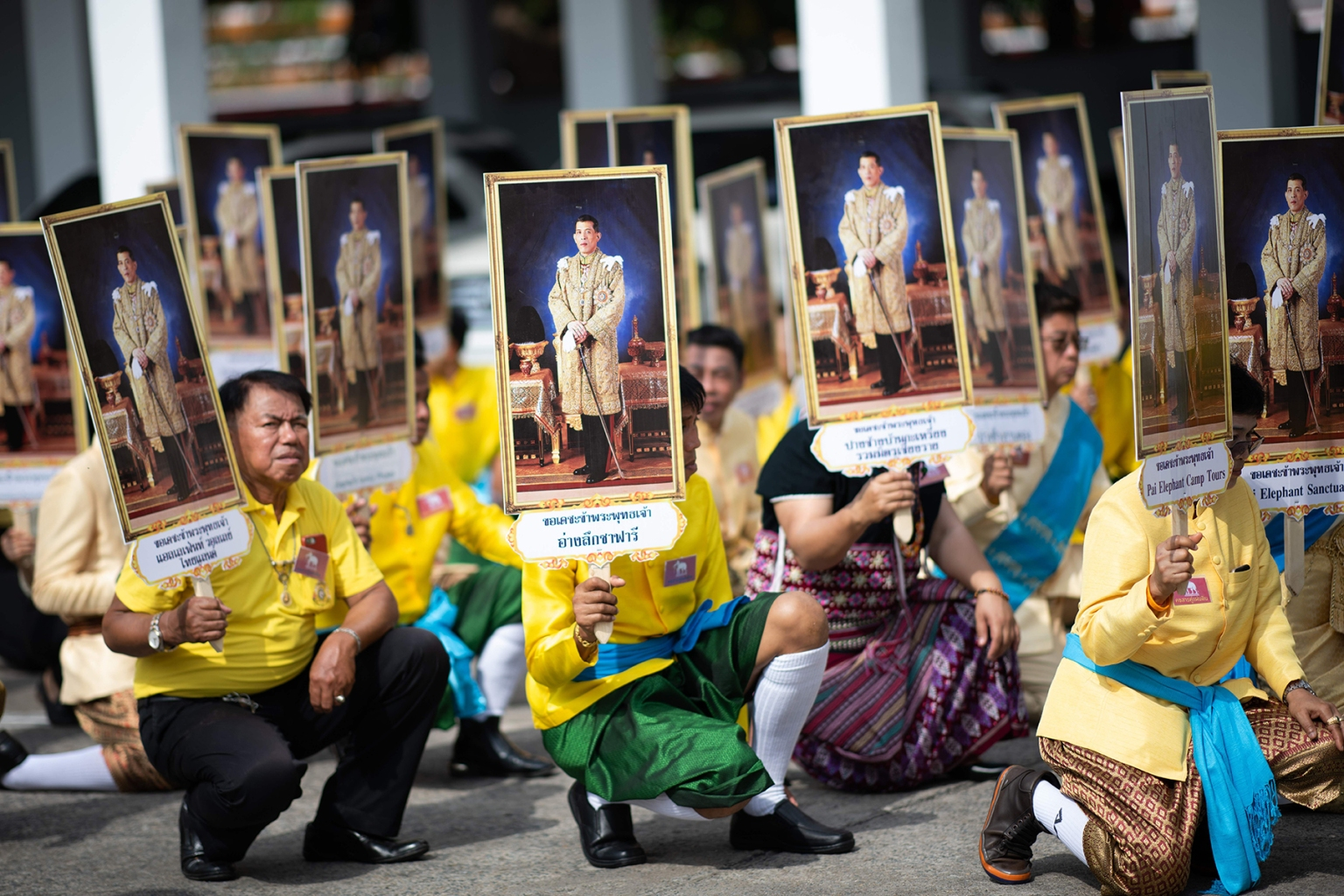 Well-wishers hold pictures of Thailand's King Maha Vajiralongkorn during a procession near the Grand Palace to pay respects to the King in Bangkok on May 7. JEWEL SAMAD/AFP/Getty Images