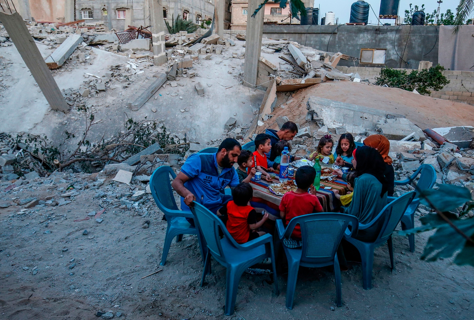 A Palestinian family break their Ramadan fast next to their house that was destroyed in the recent confrontation between Hamas and Israel in Rafah in the southern Gaza Strip on May 8. SAID KHATIB/AFP/Getty Images