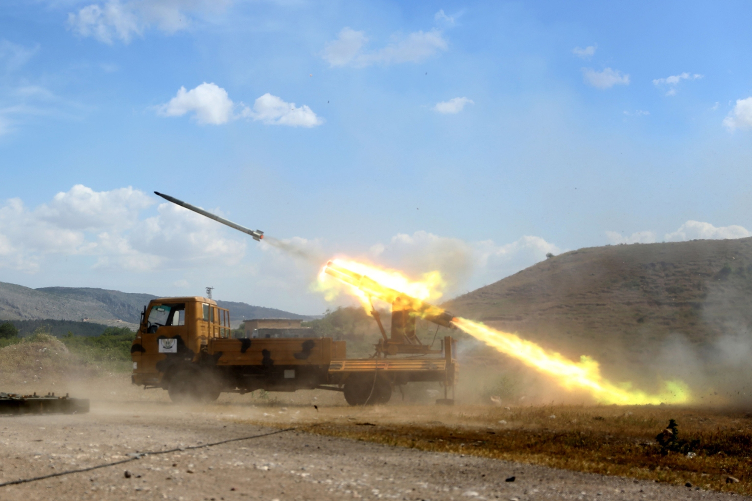 Syrian fighters from the Turkish-backed Hamza faction fire a missile from Syria's rebel-held Aleppo province toward regime-held areas on May 9. NAZEER AL-KHATIB/AFP/Getty Images