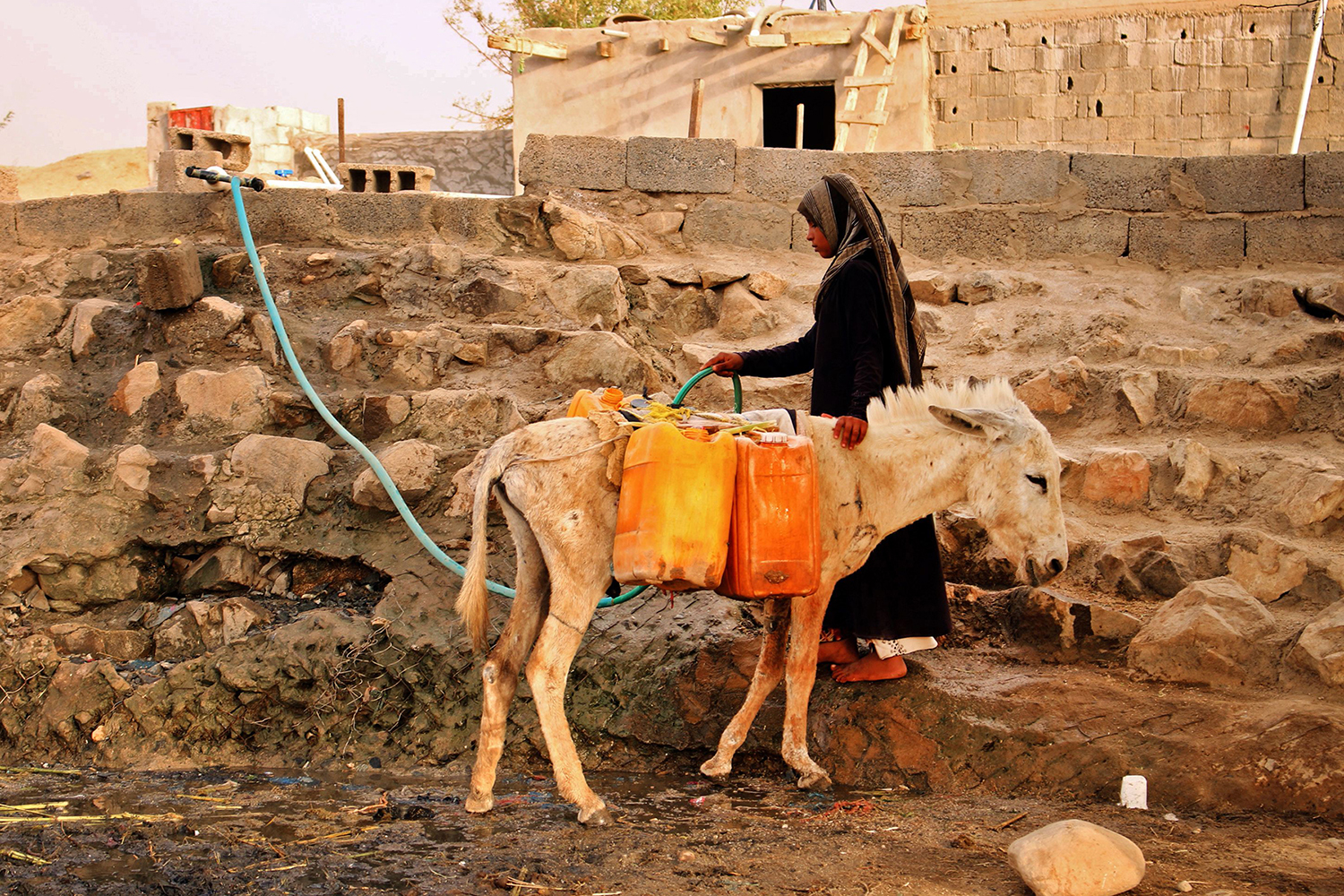 A displaced Yemeni woman from Hodeida fills water containers at a makeshift camp in a village in the northern district of Abs in the country's Hajjah province on May 9. ESSA AHMED/AFP/Getty Images