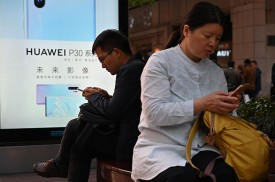 People check their mobile phones next to Huawei advertising in Shanghai, China, on May 10.