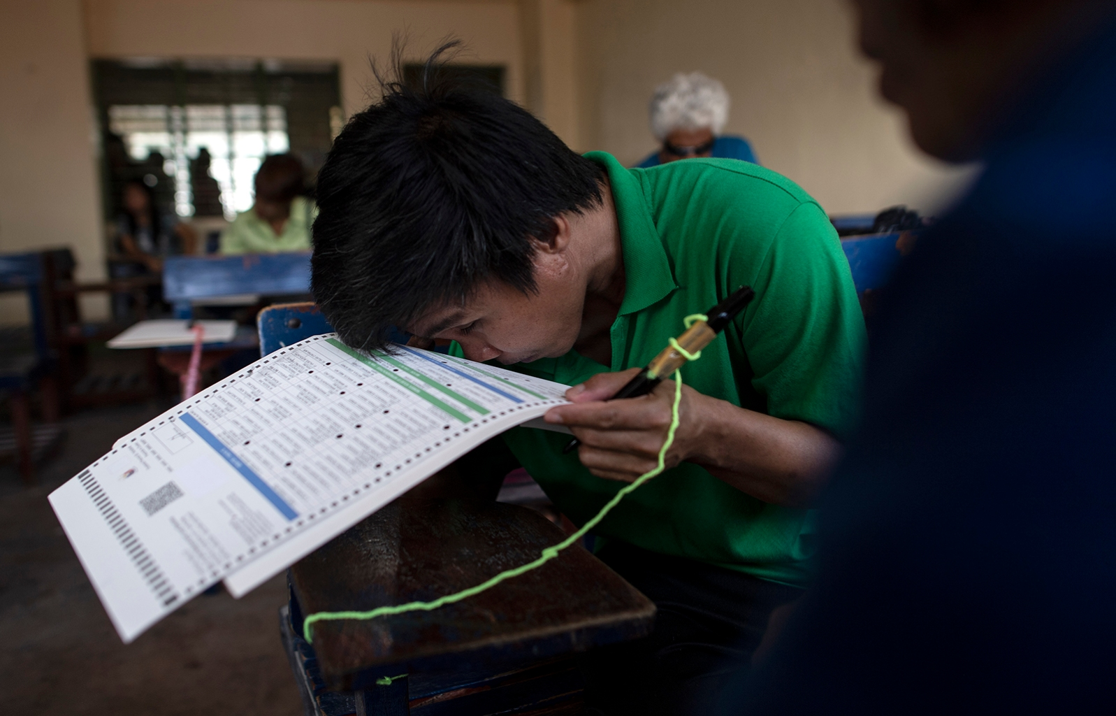 A partially blind man checks a ballot at Jose P. Laurel Senior High School in Manila on May 13 as Filipinos thronged to midterm polls that are expected to strengthen President Rodrigo Duterte's grip on power. NOEL CELIS/AFP/Getty Images
