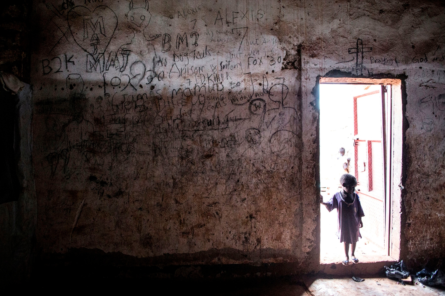 A young South Sudanese child stands on the doorstep of a building in a transition camp for refugees who have just arrived in Aru on May 12. JOHN WESSELS/AFP/Getty Images