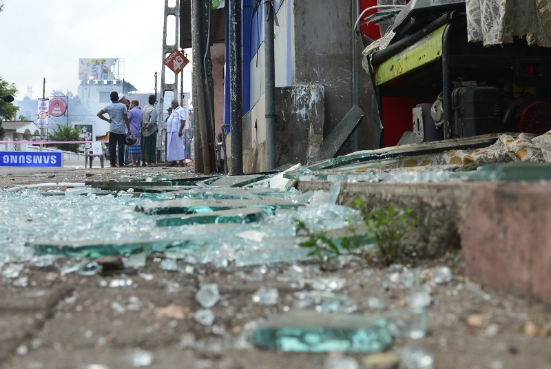 People gather near a damaged shop after a mob attack in Minuwangoda on May 14, 2019, north of the Sri Lankan capital Colombo.