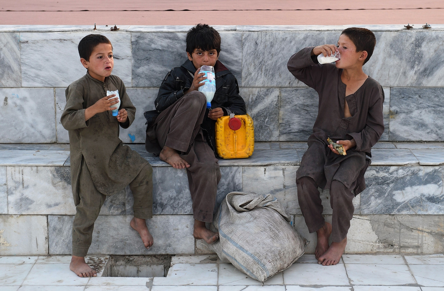 "Afghan boys enjoy yogurt-based drinks in the courtyard of the Hazrat-e Ali shrine, or ""Blue Mosque"" during the Muslim holy month of Ramadan in Mazar-i-Sharif on May 14. FARSHAD USYAN/AFP/Getty Images"