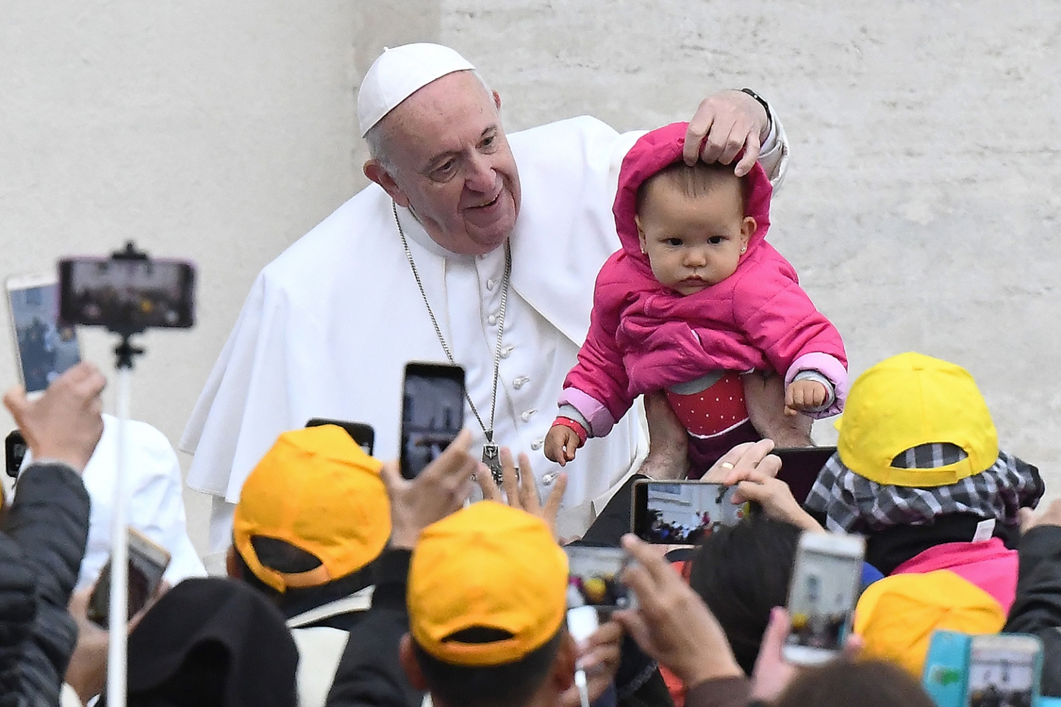 Pope Francis touches a baby as he arrives for his weekly general audience in St Peter's Square at the Vatican on May 15. VINCENZO PINTO/AFP/Getty Images