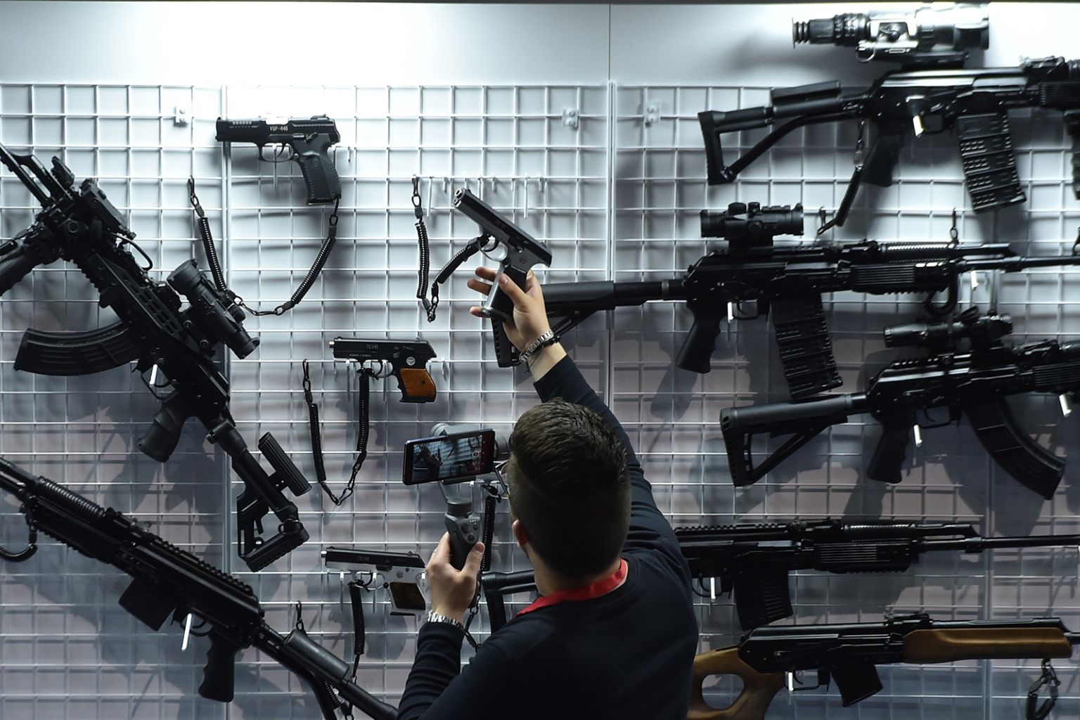 A man examines a pistol while visting the 9th International Exhibition of Arms and Military Machinery MILEX-2019 in Minsk, Belarus, on May 15. SERGEI GAPON/AFP/Getty Images