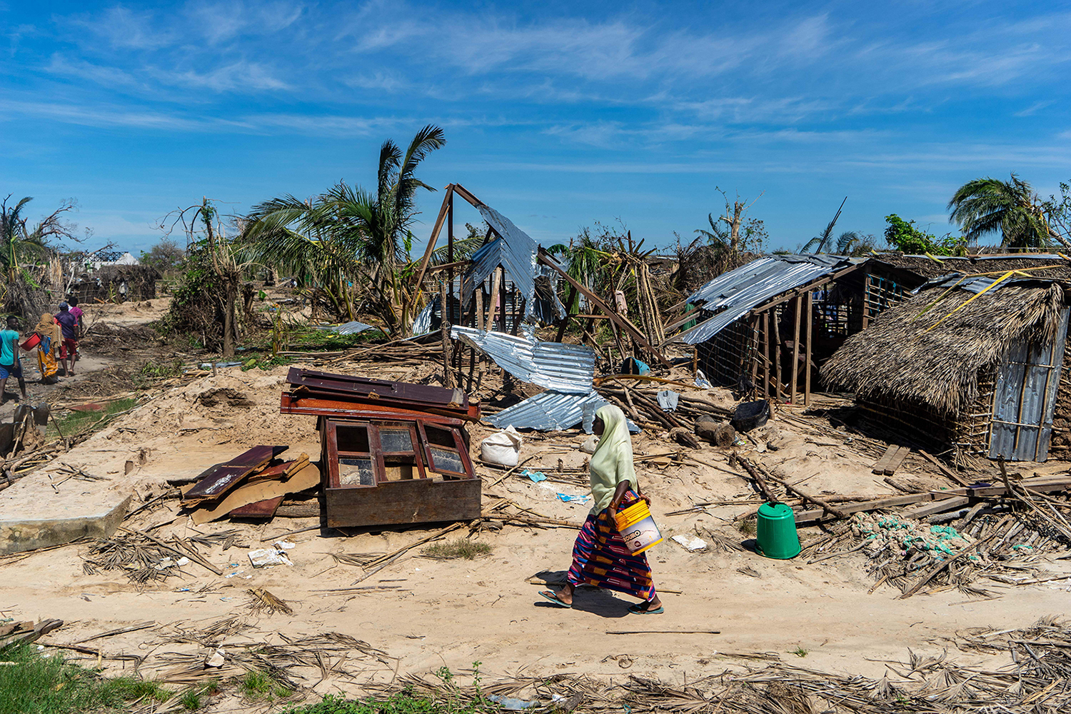 A woman walks past destroyed houses on her way to an aid distribution center in the coastal village of Guludo on Ibo Island, Mozambique, on May 13 in the aftermath of a devastating cyclone. ZINYANGE AUNTONY/AFP/Getty Images