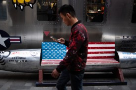 A man walks by a bench featuring a U.S. flag outside a store in Beijing on May 15.