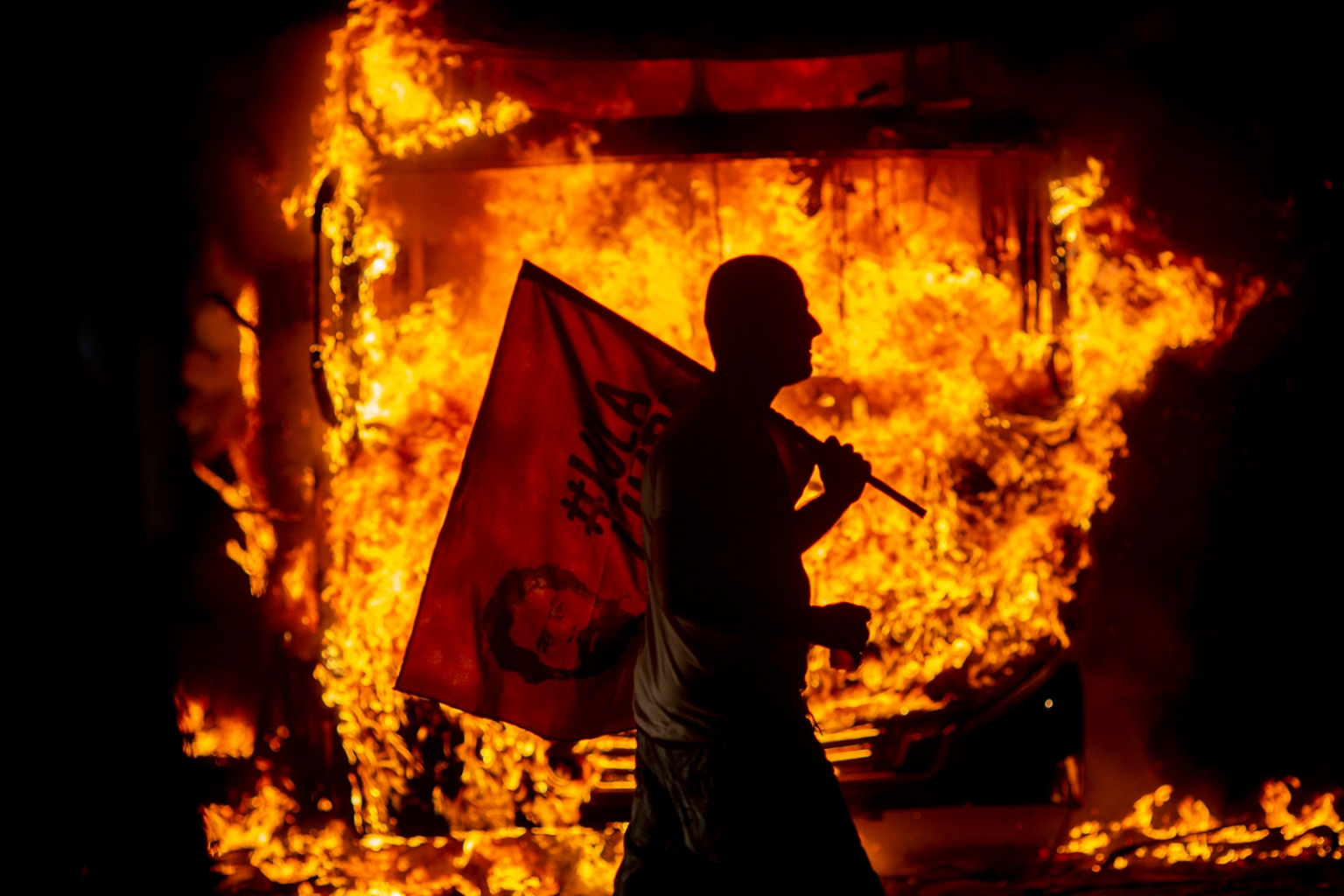 "A man holds a flag depicting former Brazilian President Luis Inacio Lula da Silva past a bus in flames during a protest organized by the National Students Union in Rio de Janeiro on May 15. Students and teachers from hundreds of universities and colleges began a nationwide demonstration in ""defense of education following a raft of budget cuts announced by President Jair Bolsonaro's government. MAURO PIMENTEL/AFP/Getty Images"