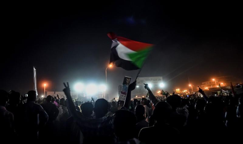 Sudanese protesters wave flags during a sit-in outside military headquarters in Khartoum on May 15.