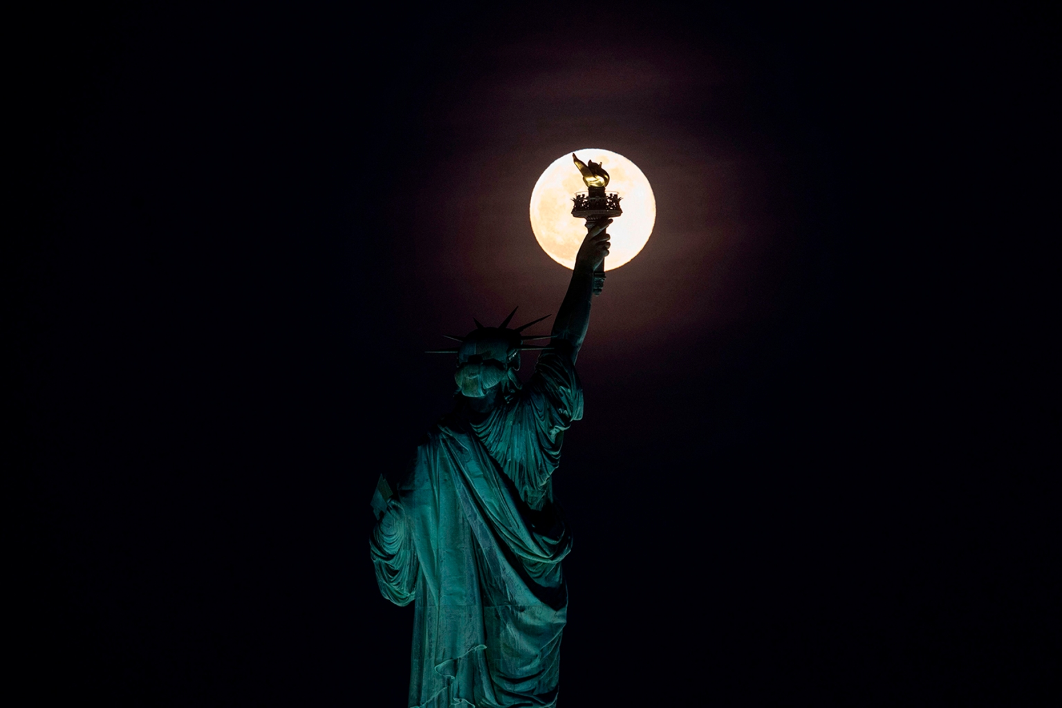 The full moon rises behind the Statue of Liberty in New York City on May 18. JOHANNES EISELE/AFP/Getty Images