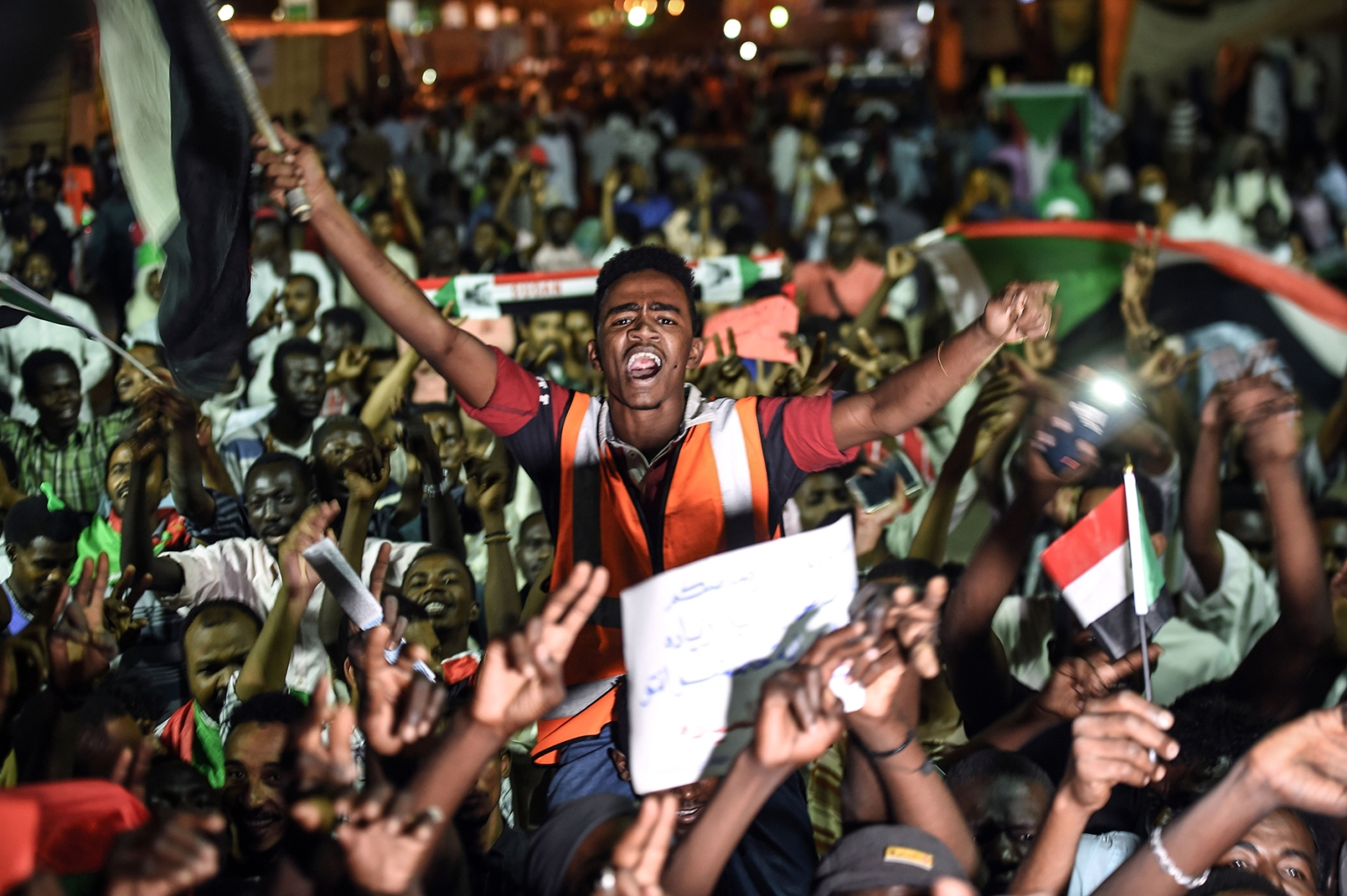 Sudanese protesters wave flags and flash victory signs as they gather for a sit-in outside the military headquarters in Khartoum on May 19. MOHAMED EL-SHAHED/AFP/Getty Images