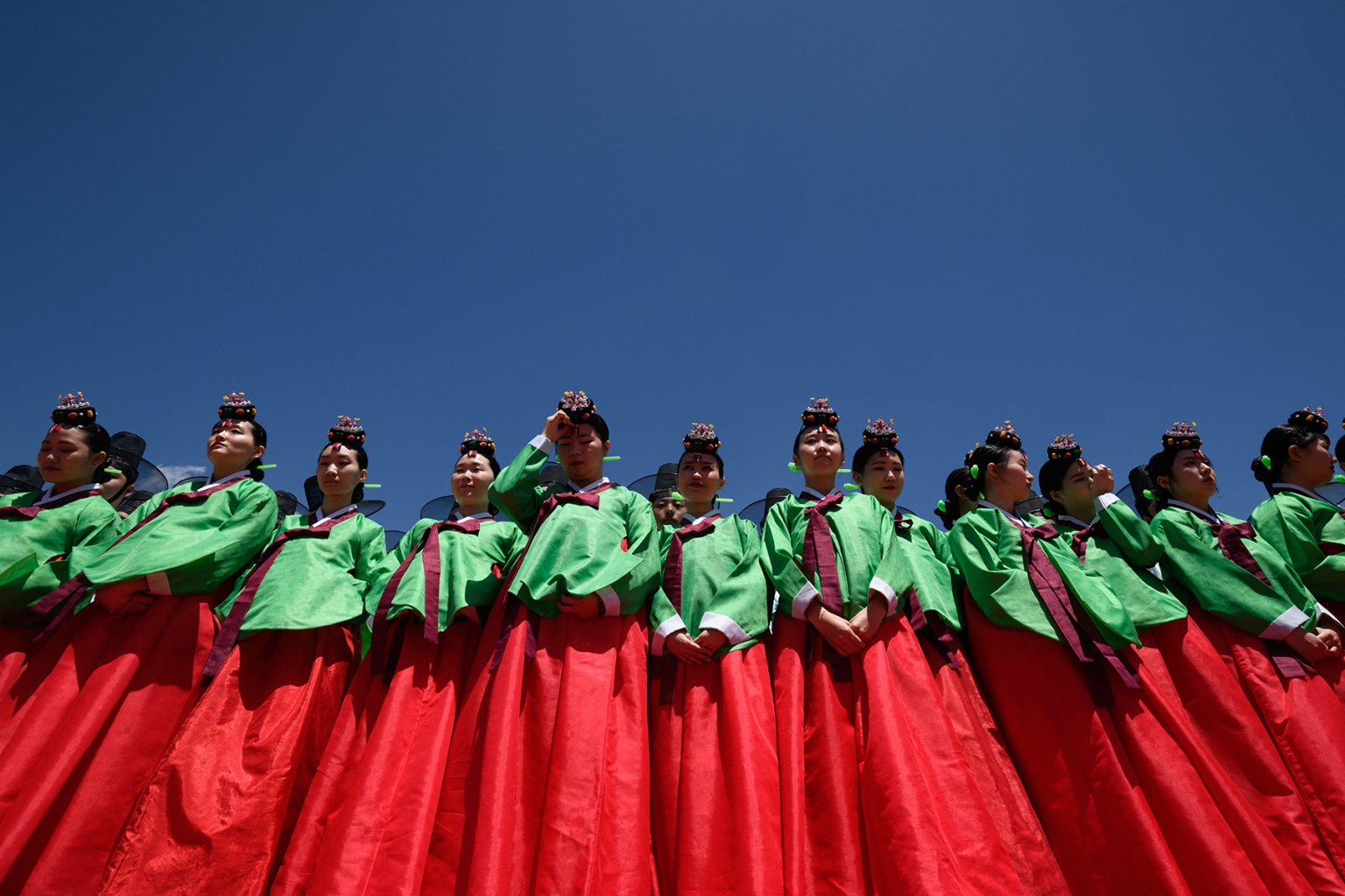 Young women wearing traditional hanbok dress line up for a group photo as they attend a traditional Coming-of-Age Day ceremony to mark adulthood at Namsan hanok village in Seoul on May 20. ED JONES/AFP/Getty Images