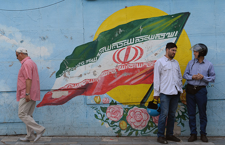 People chat in front of a mural depicting Iran's flag of Iran, in Tehran, Iran on May 22.