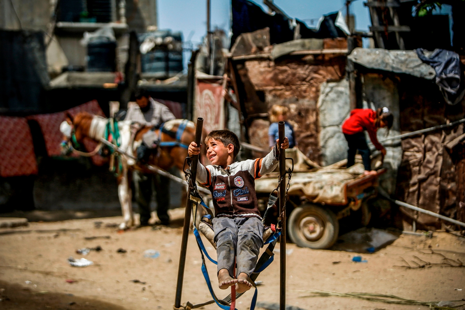 A Palestinian boy rides on a makeshift swing in an impoverished area in Beit Lahia in the northern Gaza Strip on May 22. MOHAMMED ABED/AFP/Getty Images