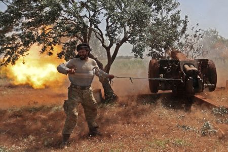 A Syrian fighter from the Turkish-backed National Liberation Front fires a heavy artillery gun from the jihadist-held Idlib province against regime positions in the northern part of Hama province on May 22. OMAR HAJ KADOUR/AFP/Getty Images