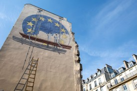 Two workers paint the European Union flag on the side of a building in Paris on May 23.