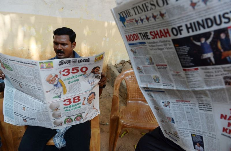 An Indian resident reads a newspaper with news of the election victory of Prime Minister Narendra Modi in Chennai on May 24.