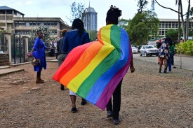 A person wearing a rainbow flag leaves the Milimani High Court in Nairobi after Kenya's high court, in a much-awaited verdict, refused to scrap laws criminalizing same-sex relationships, on May 24.