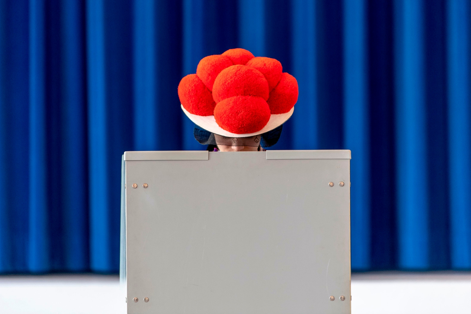A woman with a Bollenhut traditional hat stands in a voting booth during the European elections in Gutach, Germany, on May 26. PATRICK SEEGER/AFP/Getty Images
