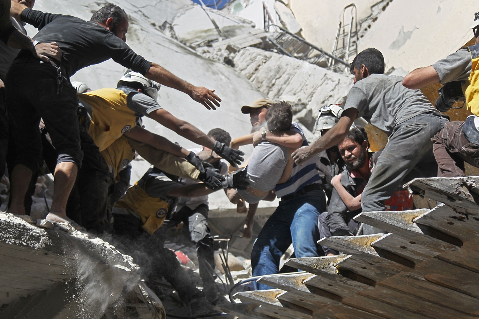 White Helmet volunteers and civilians rescue a child from the rubble of a building destroyed during an airstrike by Syrian regime forces and their allies on the town of Ariha, in the southern outskirts of Syria's Idlib province, on May 27. AMER ALHAMWE/AFP/Getty Images
