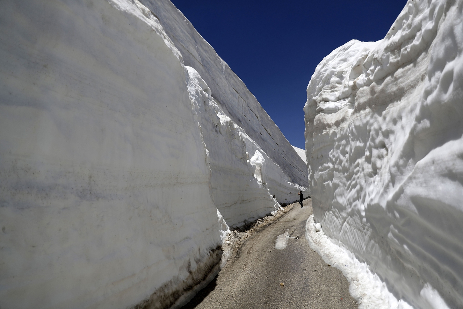 People take pictures on a road surrounded by walls of snow in the northern Lebanese village of Ainata al-Arz on May 28.  The road has been recently serviced to allow cars to access it. JOSEPH EID/AFP/Getty Images
