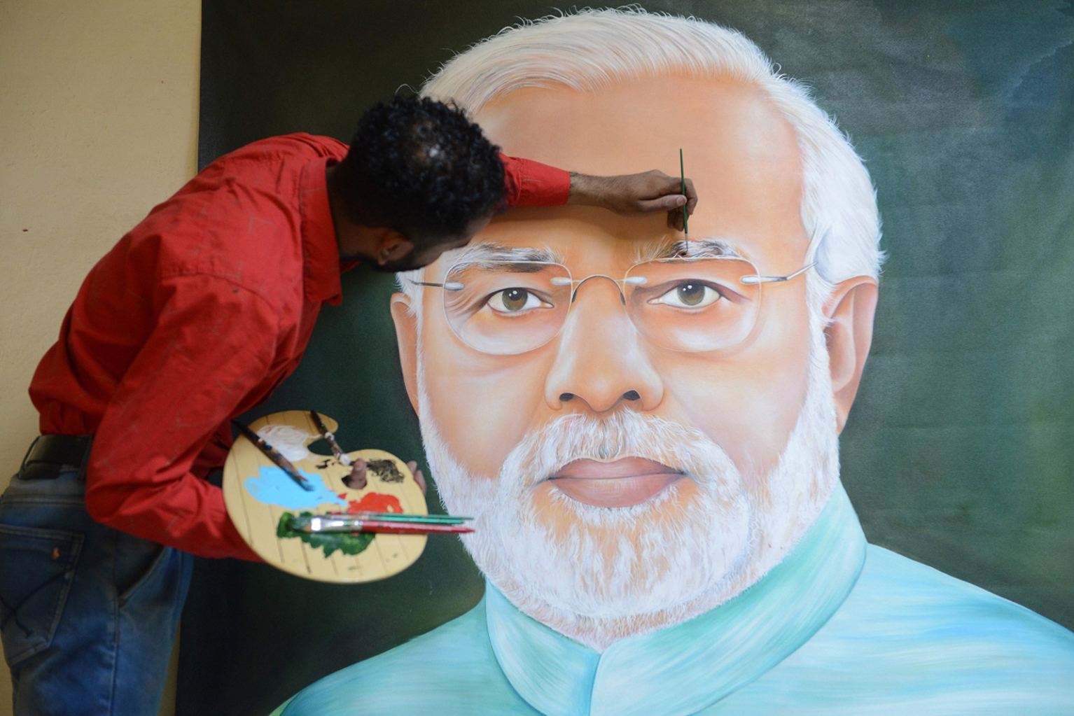 Indian painter Jagjot Singh Rubal puts the final touches on a painting of Indian Prime Minister Narendra Modi in Amritsar on May 29. NARINDER NANU/AFP/Getty Images