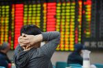 Investors watch market figures in Nanjing, China, at a stock exchange hall on May 20.