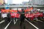A Chinese riot policeman (C) directs protesters as they march and display anti-Japanese banners during a protest over the Diaoyu islands issue, known as the Senkaku islands in Japan, in Chengdu, southwest China's Sichuan province on September 16, 2012.