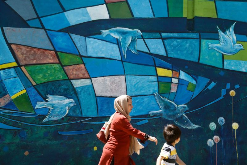 An Iranian woman and child walk past a mural in downtown Tehran on April 27, 2016.