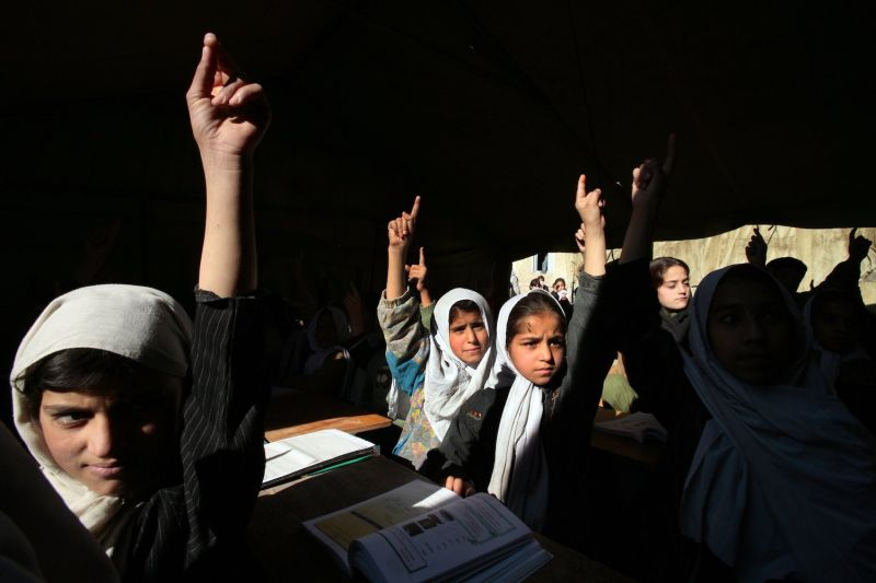 Afghan girls raise their hands during English class at the Bibi Mahroo high school in Kabul on Nov. 22, 2006.