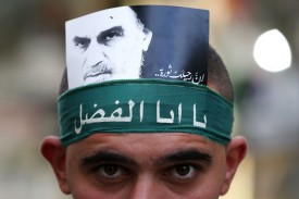 A Hezbollah supporter displays a picture of Iran's late founder of the Islamic Republic Ayatollah Khomeini as he marks Ashura in a southern suburb of the Lebanese capital Beirut on Oct. 1, 2017.