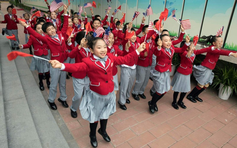 Students wave US and Chinese flags as they send off US First Lady Melania Trump and China's First Lady Peng Liyuan after their visit to the Banchang Primary School in Beijing on November 9, 2017.