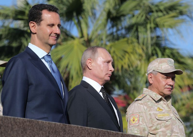 Russian President Vladimir Putin and Syrian President Bashar al-Assad inspect a military parade during their visit to the Russian air base in Hmeimim in the northwestern Syrian province of Latakia on Dec. 11, 2017.