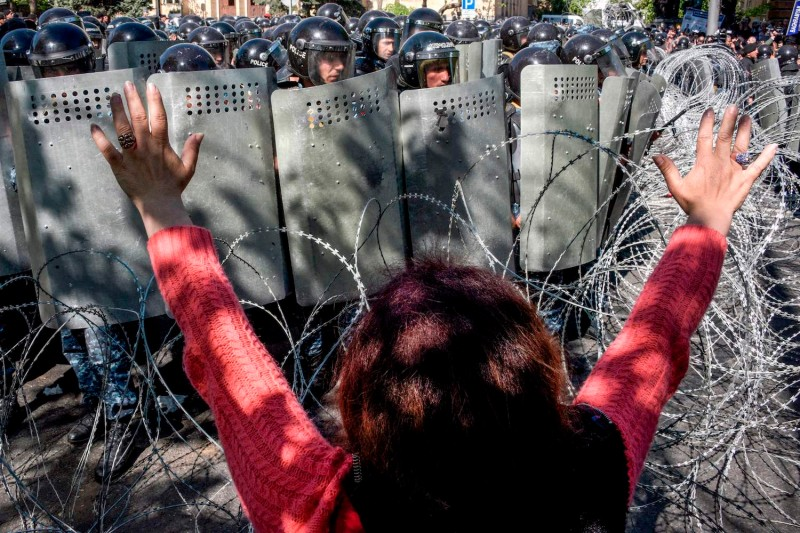 A woman gestures as Armenian special police forces block a street during an opposition rally in central Yerevan on April 16, 2018.