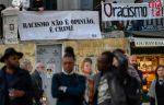 "Participants stand before signs stating ""Racism is not an opinion, it is a crime"" and ""Racism Kills!"" during the International Day for the Elimination of Racial Discrimination in Lisbon on March 21."