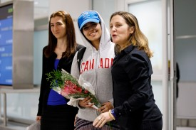 Asylum Seeker Rahaf al-Qanun smiles as she is introduced to the media at Toronto Pearson International Airport on Jan. 12, alongside Canadian minister of Foreign Affairs Chrystia Freeland.