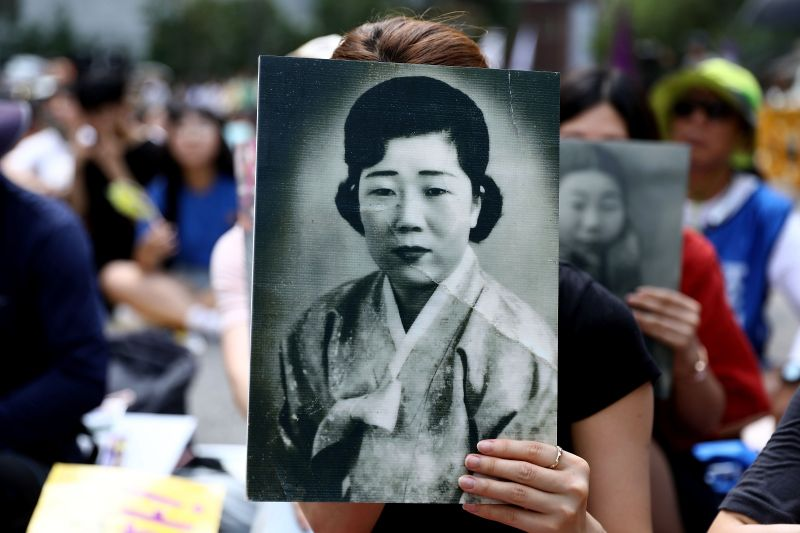 "A woman holds a portrait of a former South Korean ""comfort woman,"" one of those who were forced by Japan's military into sexual slavery during World War II, at a rally to mark National Liberation Day in front of the Japanese Embassy in Seoul on Aug. 15, 2018."