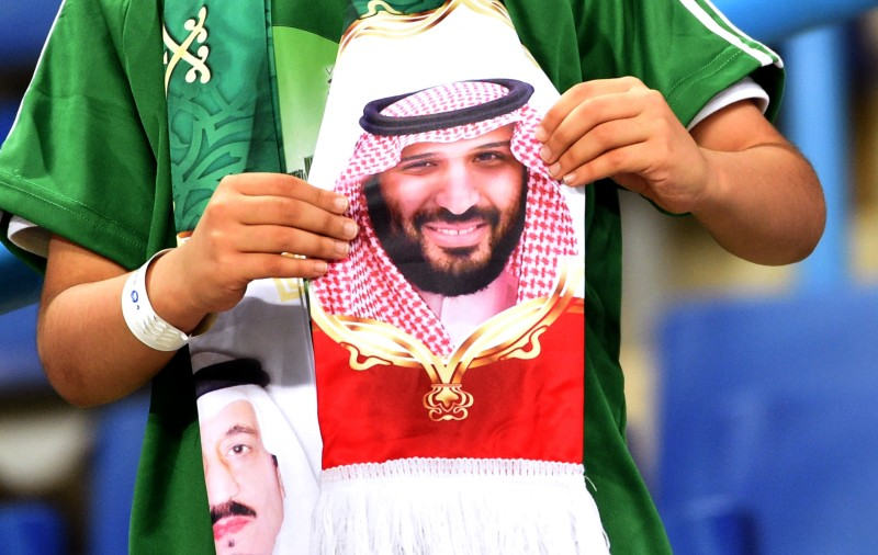 "A Saudi fan holds a scarf with portraits of King Salman and his son, Crown Prince Mohammed bin Salman, during a friendly football match between Saudi Arabia and Iraq for the ""Superclassico"" championship at King Saud University Stadium in Riyadh on Oct. 15, 2018."