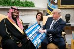 President Donald Trump shows off posters as he talks with Crown Prince Mohammad bin Salman of the Kingdom of Saudi Arabia during a meeting in the Oval Office at the White House on Tuesday, March 20, 2018 in Washington, DC. (Photo by Jabin Botsford/The Washington Post via Getty Images)