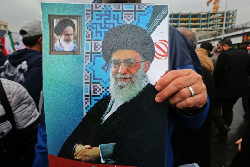 An Iranian holds up a poster showing a portrait of the country's Supreme Leader Ali Khamenei with a small portrait in the corner showing Islamic Revolution founder Ayatollah Ruhollah Khomeini, during a ceremony celebrating the 40th anniversary of Islamic Revolution in the capital Tehran on Feb. 11.