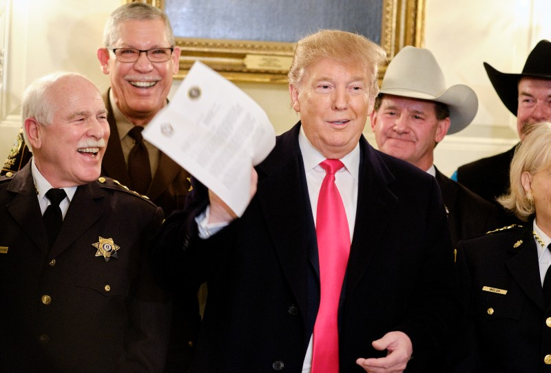 President Donald Trump jokes about a letter given to him by a sheriff after meeting with sheriffs from across the country in the Diplomatic Reception Room at the White House Feb. 11 in Washington, D.C.