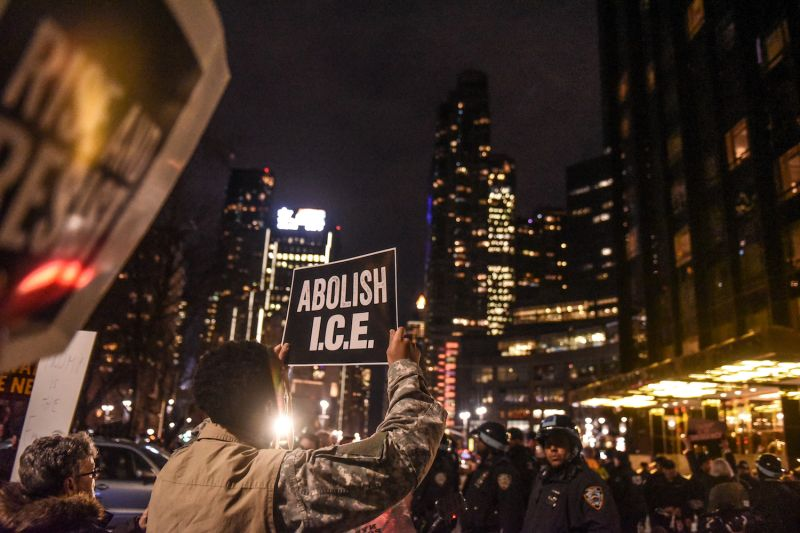 "People hold signs that read ""Abolish I.C.E."" in front of the Trump International Hotel in New York on Feb. 15."