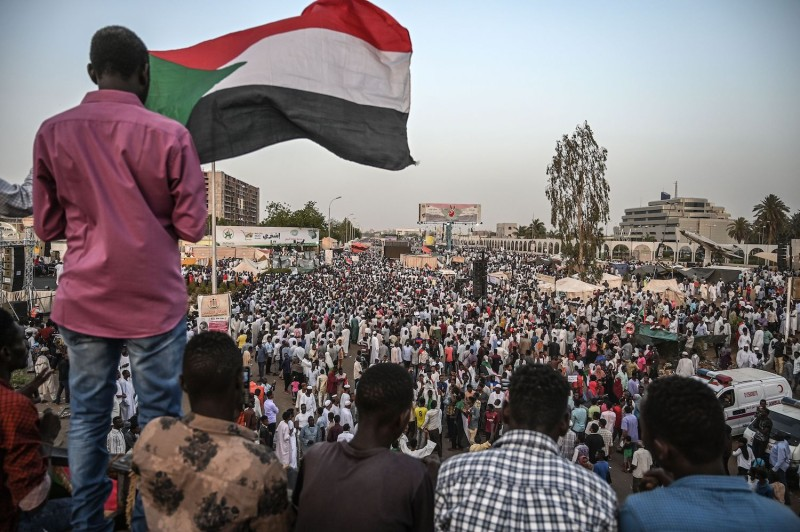 Sudanese protesters sit on a bridge during a demonstration outside the army headquarters in the capital of Khartoum on April 19.